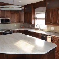 Solid surface dark kitchen cabinet doors white custom countertops Mike's Countertop Shop Sudbury Ontario.